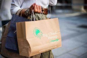 Lady shopping with paper bags with Big Chief logo