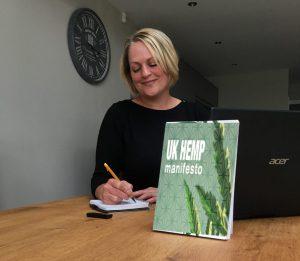Foudner mandy at desk with laptop and UK hemp Manifesto